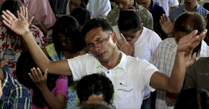 Christian man prays for the men stoning him