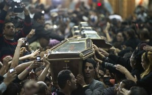 Egpytian Copts carry four coffins down the aisle of the Virgin Mary Coptic Christian church. (Photo: AFP/GETTY)