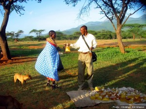 Ezekiel giving cooking oil to a Samburu woman. (Photo by Christian Aid Mission)