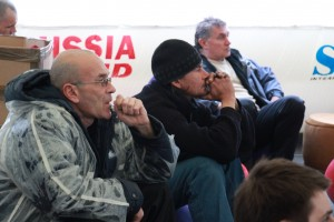 Men watching the Russian hockey game in the Fun Zone tent.