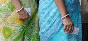 Women holding voter registration cards.  (Photo cred: Goutam Roy via Flickr)
