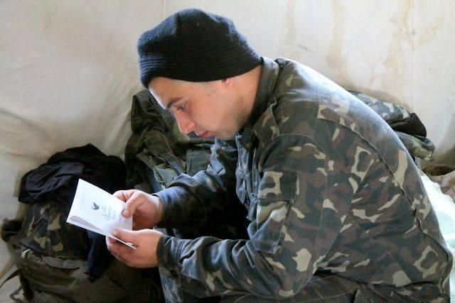 Urkrainian soldier reads Scripture.