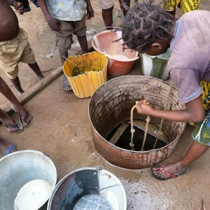 Girls fetching water from a shallow hand dug well. This is the only water source for 3,500 people at the Castor refugee center.  (Image, caption courtesy Water for Good)