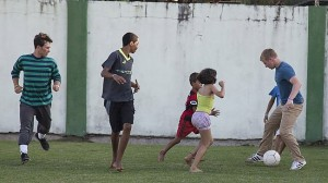 Student volunteers Dane Van Ryckeghem (far right) and Jordan O'Donnell (far left) play soccer with Brazilian children on the outskirts of Rio de Janeiro. (IMB) photo by Lina White