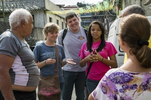 VISITING NEIGHBORS Gloria Reese (right), daughter of IMB missionaries Eric and Ramona Reese, translates for student volunteers Morgan Waters (left) and James Dubuisson (center) as they visit residents in the neighborhood surrounding Alto da Boa Vista Baptist Church in Rio de Janeiro. Photo © 2014 IMB / Wilson Hunter