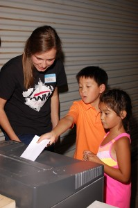 Nikki (summer intern) helping visiting students from a local Christian school summer camp  as they volunteer at the Advancing Native Missions office. (Image, caption courtesy ANM)