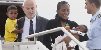 Meriam Ibrahim gets off the plane in Italy with her two children, escorted by an Italian official.