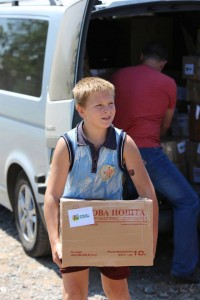 Photo of young boy helping distribute I Care boxes in Eastern Ukraine (photo provided by Russian Ministries).