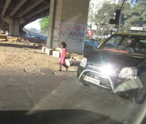 Little girl walks alone in the busy streets of Mumbai.  (Photo courtesy Katey Hearth)