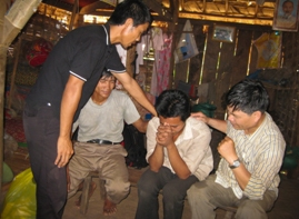 Evangelists pray for an ethnic Khmu who has decided to put his trust in Christ