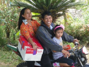 Smiling faces of a family who just received free Christian literature (Photo courtesy of Christian Resources International)