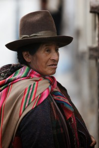 A quechua woman, wearing a tall, brimmed hat and carrying woven belts on her back in a colorful, cloth sling, walks the streets of Cusco, Perú, selling the hand-crafted belts to tourists. (Photo, caption courtesy of Nathan Gibbs via Flickr) cc2.0