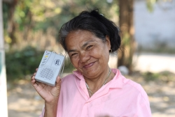 A Thai woman listens to a Christian program on her SonSet radio fixed-tuned to a local community station (Photo and caption by Reach Beyond).