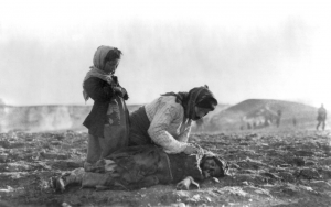 """Armenian woman kneeling beside dead child in field """"within sight of help and safety at Aleppo""""  (Caption, photo courtesy Wikipedia)"""