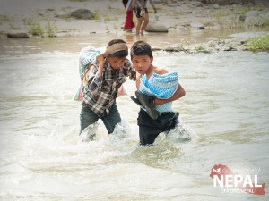 Two Nepali boys help each other cross the river, carrying 66 lbs. rice and a tent after a recent relief distribution event. (Photo, caption courtesy GFA)