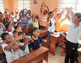 (Photo courtesy Compassion International)  A teacher, adult woman, wearing a staff shirt and jeans, stands in front of her class, leading her students, classroom children, boys and girls, sitting and standing in wooden rows of desks, in fun and educational classroom learning activities and song, singing.