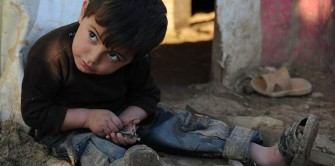 A small refugee boy finds some nails to play with outside the run-down building where his family has taken shelter in Lebanon.  (Photo, caption courtesy Christian Aid Mission)