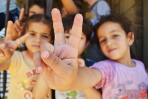 Syrian refugee children at a half-built apartment block near Reyfoun in Lebanon, close to the border with Syria, give the peace sign. The families fled Syria due to the war and are now living on a building site. (Photo: Eoghan Rice via Flickr)