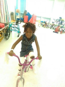 She not only walks, but can ride her bike! (Photo courtesy of For Haiti with Love).