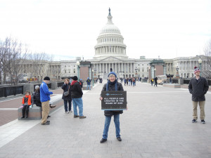 Michele Shoun with her sign in front of the Capitol. (Caption, photo courtesy of Life Matters Worldwide via Facebook)