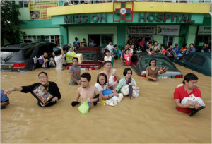 People wading through the water outside the hospital [in the Philippines]. (Photo, caption courtesy of World Mission)