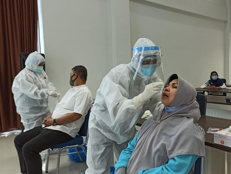 The header image shows people getting tested for COVID-19 in Indonesia. (Photo courtesy of Wikimedia Commons, Public Domain)